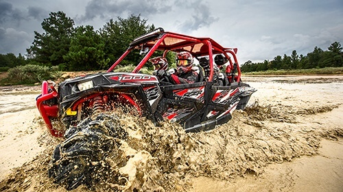 Red and Black Polaris UTV riding through mud puddle