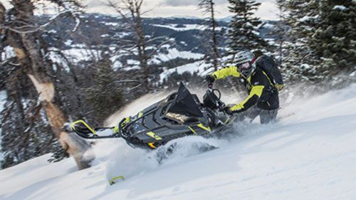 Yellow and Black Polaris Snowmobile riding through the snow